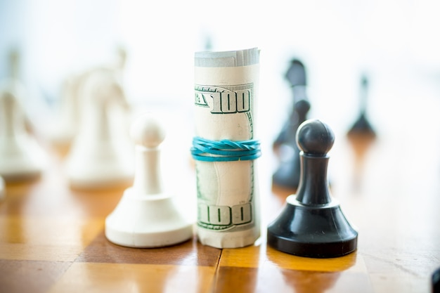 Closeup conceptuele verdraaide dollarbiljetten staan op schaakbord tussen witte en zwarte stukken