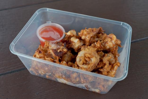Closeup diep krokant gebakken gesneden inktvis met knoflook geserveerd in afhaalcontainer met chilisaus op houten tafel