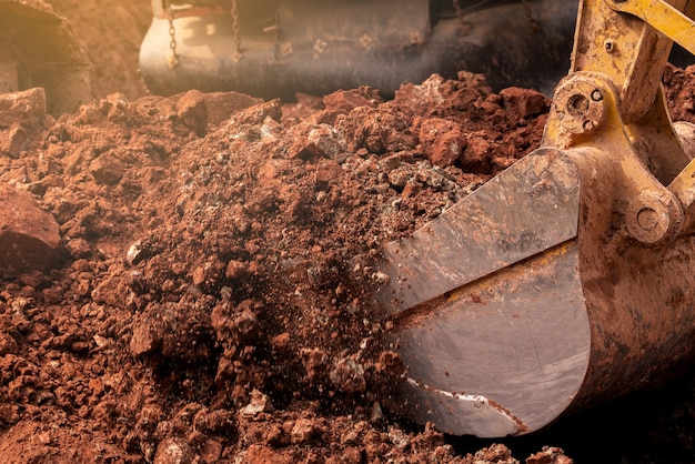 Closeup emmer backhoe graven van de grond op de bouwplaats. graafmachine.