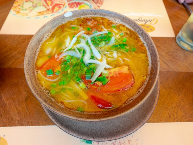 Closeup gele curry pho of vietnamese rijstnoedelsoep met groentenkom op tafel