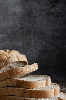 Closeup gesneden graan volkoren brood op donkere rustieke houten achtergrond bio ingrediënten