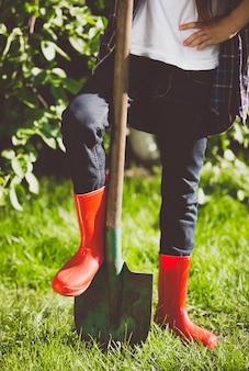 Closeup getinte jonge vrouw met been in rubberen laarzen op schop in de tuin