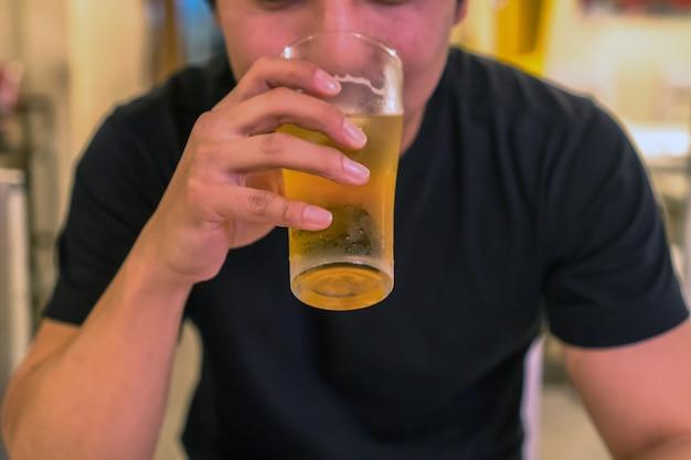Closeup hand met glas bier uit aziatische jongeman in geluk actie in pub