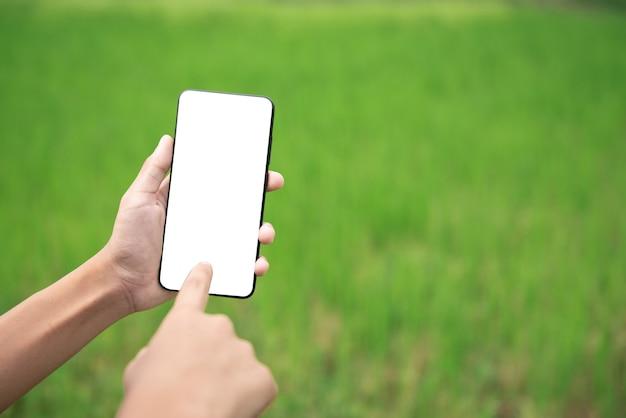 Closeup hand met smartphone met leeg scherm buitenshuis mobiele telefoon leeg wit scherm mockup
