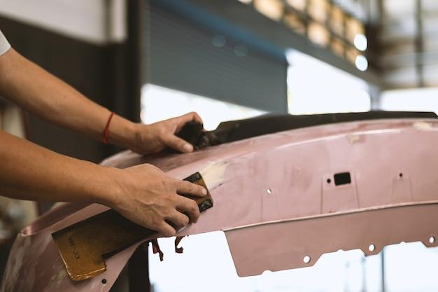 Closeup hand monteur werknemer schuren polijsten auto lichaam en voorbereiden op schilderij bij station service