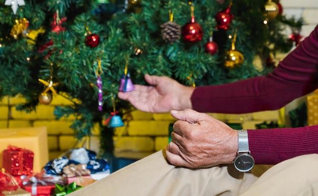 Closeup hand van senior man op knie met kerstboom achtergrond versieren. eenzaam vakantieconcept. het vieren van kerstmis en nieuwjaar activiteit.