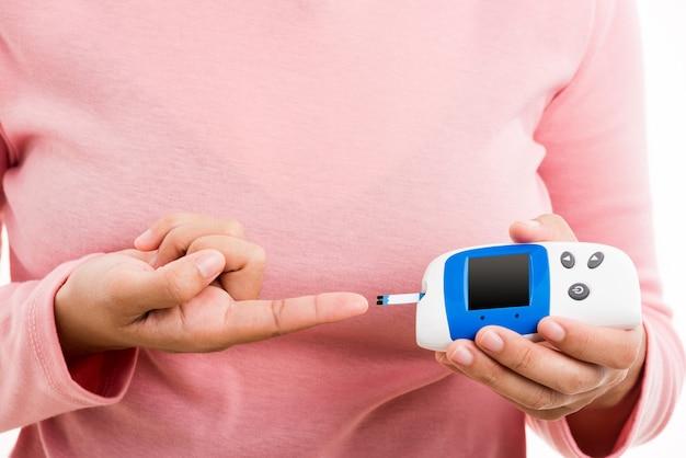 Closeup hand vrouw meten glucose test niveau controleren op vinger door glucometer
