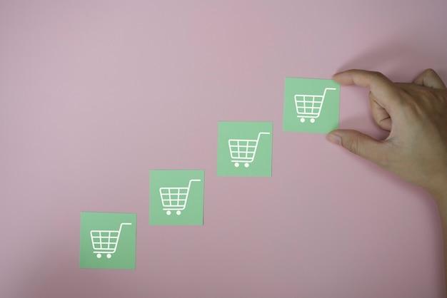 Closeup handen met pictogram papier knippen met pictogram winkelwagen symbool