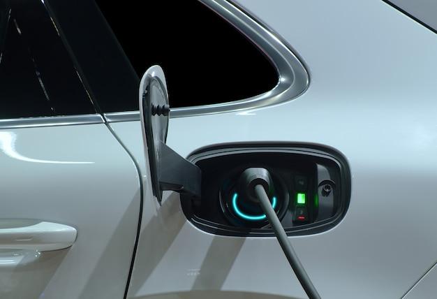 Closeup handgreep stekker aangesloten op socket lading op witte elektrische auto voor oplaadbare batterij