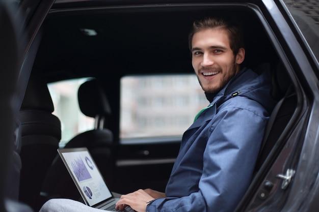 Closeup.handsome zakenman zitten in luxe limousine, werken op laptopcomputer