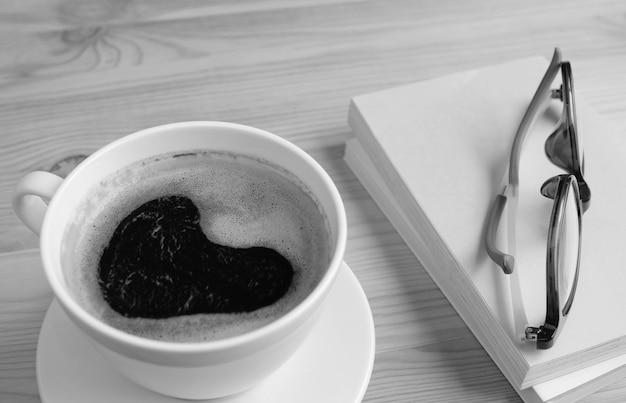 Closeup hartvorm schuim van zwarte koffie met boeken en glazen in zwart-wit
