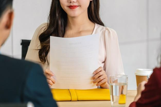 Closeup jonge aziatische afgestudeerde vrouw die het cv-document vasthoudt en zich voorbereidt op twee managers