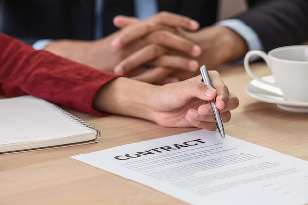 Closeup jonge aziatische vrouw afgestudeerde hand ondertekening van het contract na deal interview