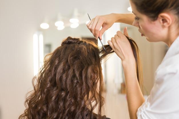 Closeup kapper coiffeur maakt kapsel voor jonge vrouw