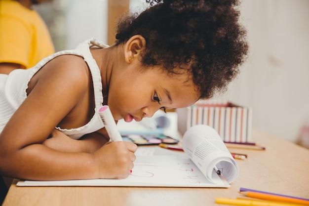 Closeup klein kind meisje zwarte huid schrijven huiswerk thuis.