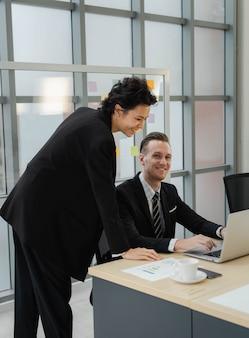 Closeup knappe blanke zakenman glimlach en kijken naar camera gelukkig werken met zakenvrouw met behulp van laptop. positieve stemming samen te werken met partnerschap. collega relatie op kantoor.