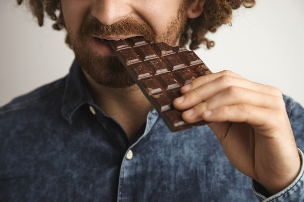 Closeup krullend haar gelukkig bebaarde man met gezonde huid bijt biologische versgebakken chocoladereep met zijkant van de mond, focus op mond