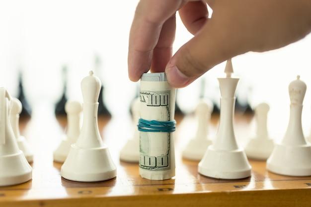 Closeup man zet in schaakspel met gedraaide bankbiljetten