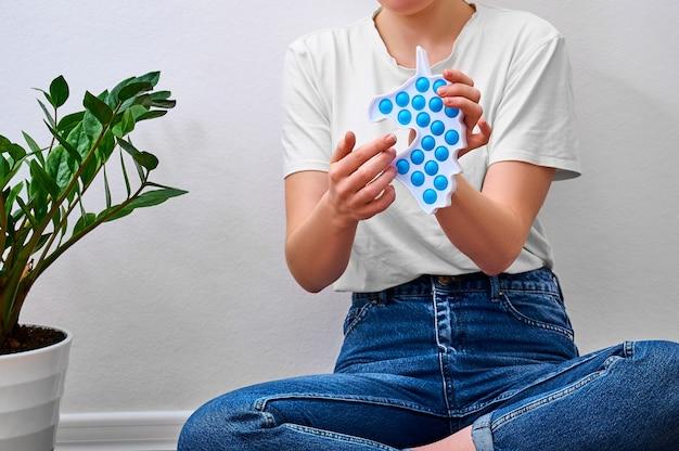 Closeup meisje houdt in handen trendy eenvoudig kuiltje speelgoed in de vorm van een eenhoorn