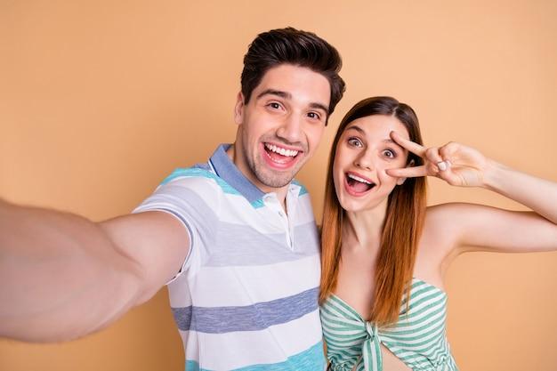 Closeup mooie vrouw dame knappe echtgenoot man getrouwd stel tijd samen doorbrengen nemen selfies goed humeur toon v-teken symbool dragen casual kleding geïsoleerd pastel beige