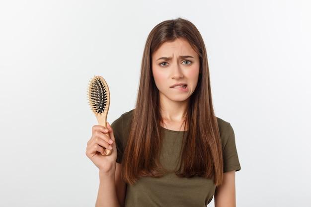 Closeup ongelukkige gefrustreerde jonge vrouw verrast dat ze haar verliest, merkte gespleten haarpunten terugwijkende haarlijn. grijze achtergrond