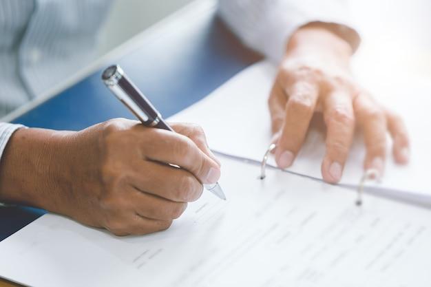 Closeup oudere hand schrijfpapier werken met balpen in bureau.