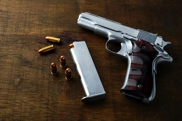Closeup pistool met gouden scherpe kogels houten tafel achtergrond