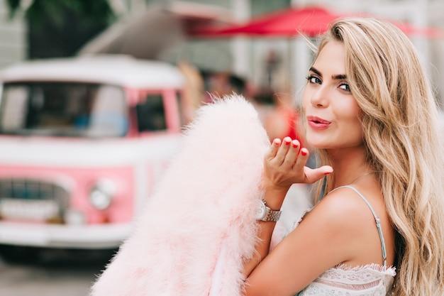 Closeup portret aantrekkelijk meisje roze bont stal in de hand houden op retro auto achtergrond. ze stuurt een kus naar de camera.