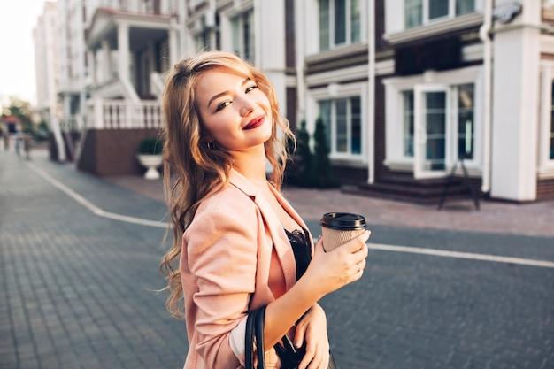 Closeup portret aantrekkelijk model met vineuse lippen wandelen met koffie in koraal jasje op straat.