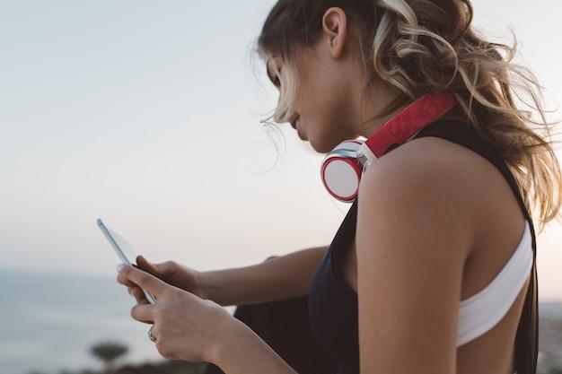 Closeup portret aantrekkelijke sportvrouw met koptelefoon op nek, lang krullend haar chatten op de telefoon, genieten van zonsopgang aan de kust. vrolijke sfeer, heerlijke zomertijd.
