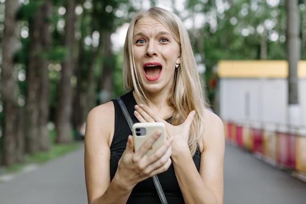 Closeup portret angstig jong meisje kijken naar telefoon zien van slecht nieuws of foto's met walgelijke emotie op haar gezicht geïsoleerd buiten de stad achtergrond. menselijke emotie, reactie, expressie