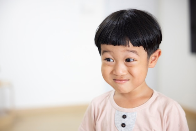 Closeup portret aziatische kind jongen recht zwart haar draagt een lichtbruin shirt kijkend naar de camera