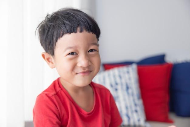 Closeup portret aziatische kind jongen recht zwart haar draagt een rood shirt kijkend naar de camera