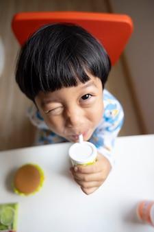 Closeup portret aziatische kind jongen recht zwart haar draagt een witte pyjama met camera kijken