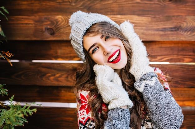 Closeup portret brunette mooi meisje met lang haar in gebreide grijze muts en winter trui op houten. ze raakt gezicht met handen in handschoenen en glimlacht.