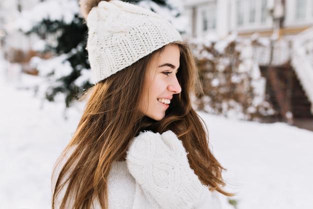 Closeup portret charmante jonge vrouw in witte wollen handschoenen, gebreide muts, lang donkerbruin haar genieten van koud winterweer op straat. lachend naar de andere kant, echte positieve emoties, opgewekte stemming.