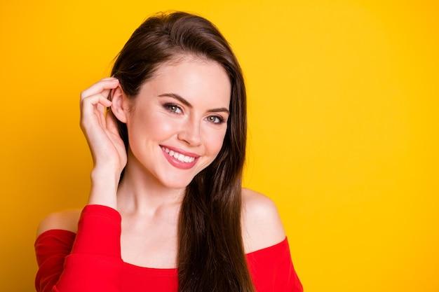 Closeup portret foto van vrij mooie mysterieuze jonge dame handen haar oor glanzende glimlach poseren tijdschrift casting slijtage shirt onbedekte schouders geïsoleerd levendige gele kleur achtergrond
