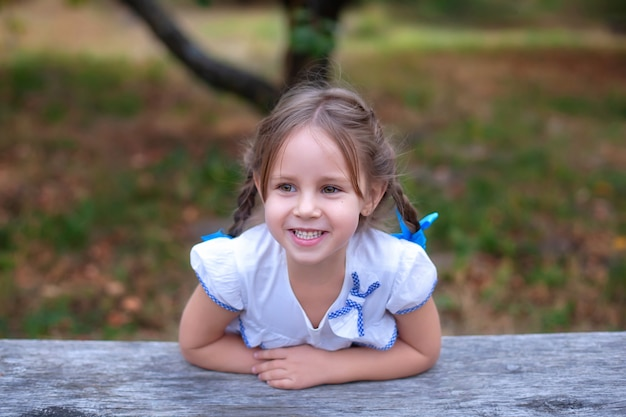 Closeup portret gelukkig lachend meisje met grote ogen en twee vlechten op haar hoofd in de tuin. glimlachend mooi kind.