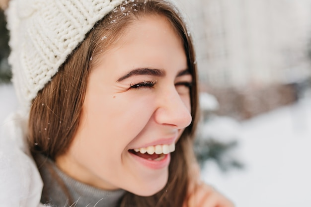 Closeup portret helder positieve gezicht emoties van vrolijke vrouw in warme witte gebreide muts lachen op straat vol met sneeuw. echte emoties, sneeuwvlokken, plezier maken, genieten van de winter.