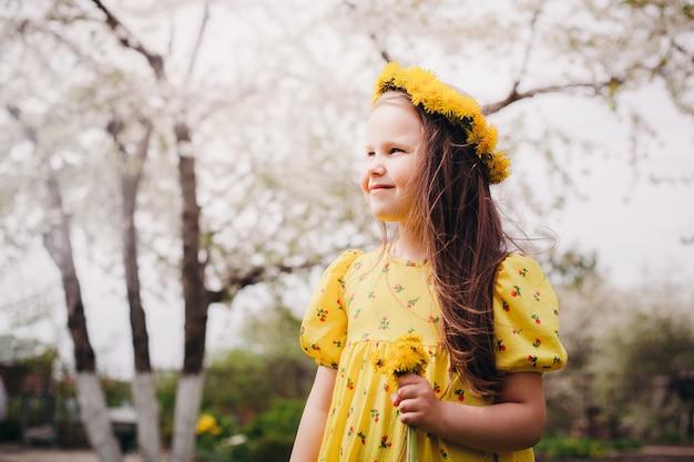 Closeup portret in profiel van een lachend meisje in een gele jurk en een krans van gele paardebloemen op...