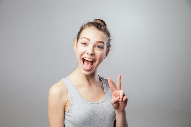 Closeup portret jonge aantrekkelijke blonde vrouw, student, mooi meisje met v vingers bewegen, geïsoleerde grijze achtergrond. positieve menselijke emoties, gezichtsuitdrukkingen, houding