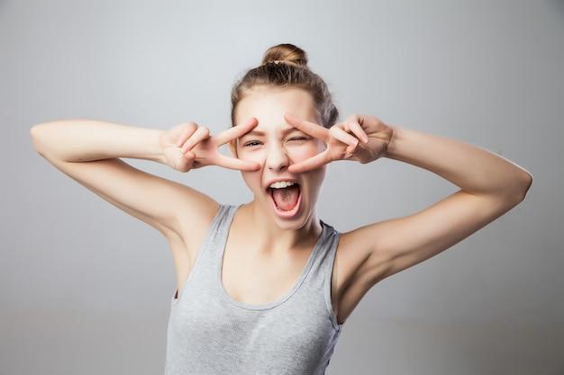 Closeup portret jonge aantrekkelijke blonde vrouw, student, mooi meisje met v vingers over de gezichtsbeweging, geïsoleerde grijze achtergrond. positieve menselijke emoties, gezichtsuitdrukkingen, houding