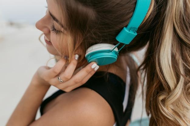 Closeup portret jonge vrouw met lang krullend haar genieten van mooie muziek via blauwe koptelefoon. lopend aan de kust, lachend met gesloten ogen, opgewekte stemming