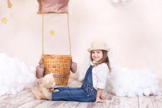 Closeup portret schattige lachende meisje, zittend op de muur van een ballon, sterren en wolken en met een teddybeer. klein meisje droomt. meisje speelt in de kinderkamer met een stuk speelgoed. jeugd
