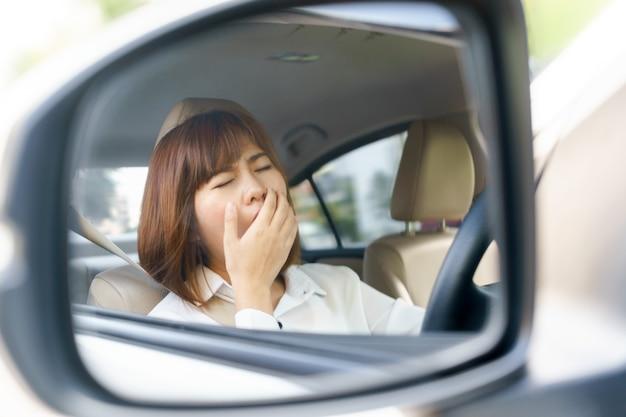 Closeup portret slaperig, moe jonge vrouw haar auto rijden na lange uur reis in de spiegel