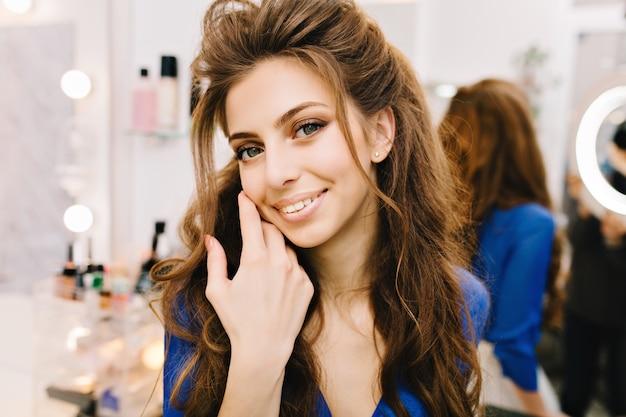 Closeup portret stijlvolle schattige jonge vrouw met lang donkerbruin haar glimlachend naar camera in kapsalon