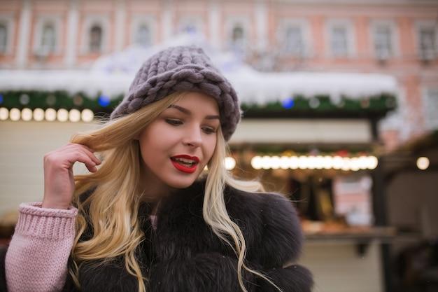 Closeup portret van aantrekkelijke blonde vrouw met lichte make-up poseren op de kerstmarkt