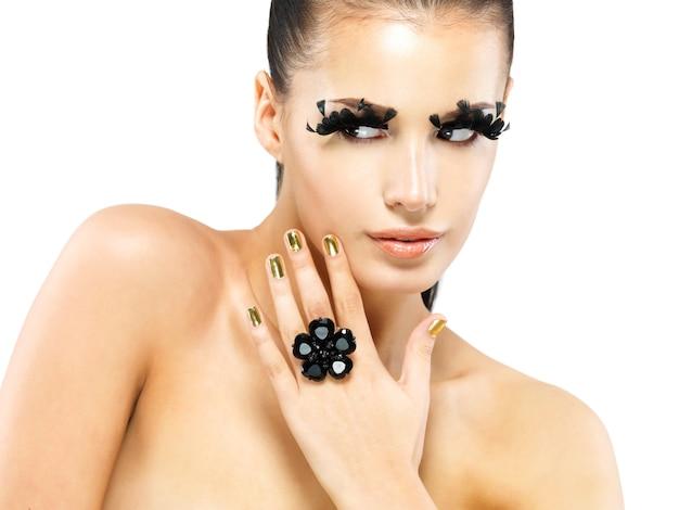 Closeup portret van de mooie vrouw met lange zwarte valse wimpers make-up en gouden nagels. geïsoleerd op witte achtergrond