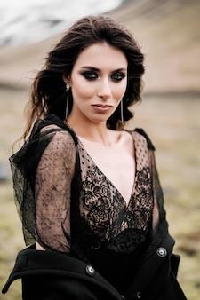 Closeup portret van een bruid in een zwarte jurk met een zwarte jas en onbeschofte make-up staat in een veld