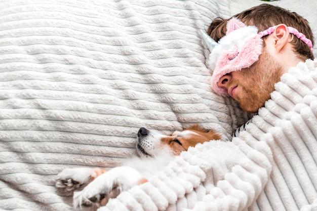 Closeup portret van een jonge man in een roze masker slapen in een bed onder een tapijt met zijn hond. ruimte kopiëren